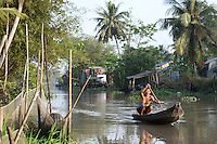 A fisherman is paddling in a canal built in the Mekong delta, Can Tho province, Vietnam - 2010
