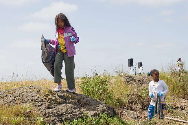 Oakland CA Preteen girls involved in beach clean up on shores of San Francisco Bay on.Earth Day