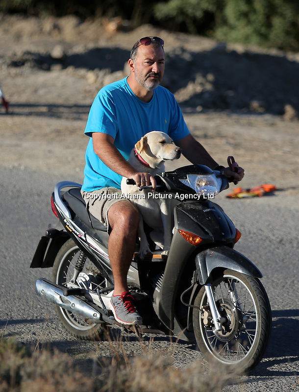 Pictured: A local man takes his labrador dog for a ride on his Honda Innova ANF 125 past the second site in Kos, Greece. Saturday 15 October 2016<br /> Re: Police teams led by South Yorkshire Police are searching for missing toddler Ben Needham on the Greek island of Kos.<br /> Ben, from Sheffield, was 21 months old when he disappeared on 24 July 1991 during a family holiday.<br /> Digging has begun at a new site after a fresh line of inquiry suggested he could have been crushed by a digger.