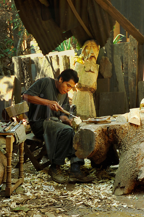 Wood carver of religious icons at work. Patzcuaro Michoacan Mexico.