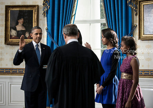 Malia Obama (2R) and Sasha Obama (R) watch as United States Supreme Court Chief Justice John Roberts, Jr. (2L) administers the oath of office as US President Barack Obama (L) is sworn in for a second term as President in the Blue Room of the White House January 20, 2013 in Washington, DC. Obama was officially sworn in for his second term as the 44th President of the United States during the 57th Presidential Inauguration but will also participate in a ceremonial swearing in on Monday. .Credit: Brendan Smialowski / Pool via CNP