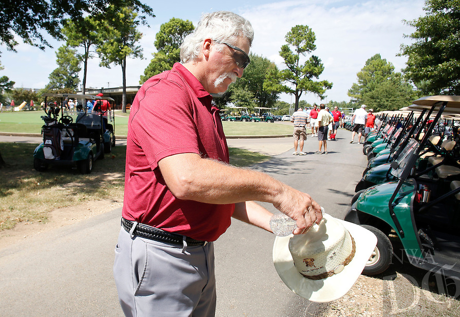 NWA Democrat-Gazette/DAVID GOTTSCHALK  Joe Rose, with Rose Electric, pours a bottle of water on his hat for absorption Friday, September 9, 2016, before the start of the 8th Annual Salvation Army of Northwest Arkansas Charity Golf Tournament at Paradise Valley Golf Course in Fayetteville. Funds raised by the event go to the new Pathway of Hope Program that will aid families move from intergenerational poverty to hope and stability.