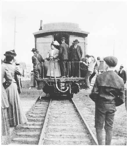 End view of passenger car with several people on the platform and nearby.<br /> D&amp;RGW  Lake City ?, CO