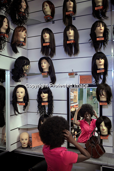 SOWETO, SOUTH AFRICA OCTOBER 5: A woman tries on an Afro wig hair piece in a shop on October 5, 2012 at Maponya shopping Mall, Soweto, South Africa. Maponya is one of several new shopping malls in the township. Soweto today is a mix of old housing and newly constructed townhouses. The population in Soweto is estimated to be around one million people. A new hungry black middle-class is growing steadily. Many residents work in Johannesburg but the last years many shopping malls have been built, and people are starting to spend their money in Soweto. (Photo by: Per-Anders Pettersson)