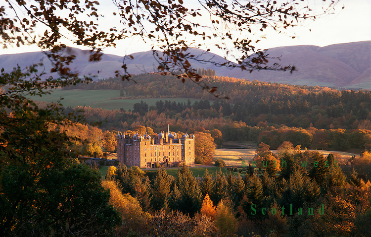 Drumlanrig Castle in a autumn landscape catching the morning sunshine with Lowther Hills behind Scotland UK