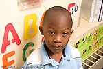 Preschool ages 3-5 portrait of boy with alphabet letters on wall behind him horizontal