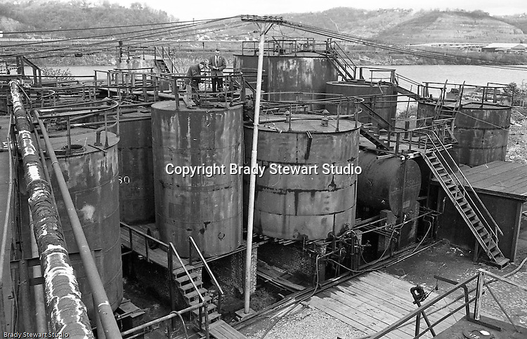 Lawrenceville PA: Location photography at the Atlantic Refining site at 5733 Butler Street. View of workman and manager checking the oil level inside one of the storage tanks.<br />
