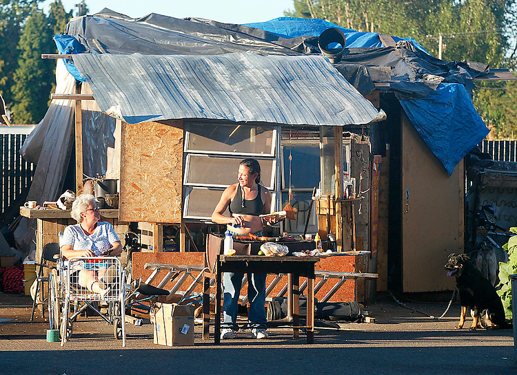 "PDX9-DIGNITY VILLIAGE-FOR  HELEN HEALY-(9/25/03)-.Mary Mazuca, right, cooks dinner while LLeanne, left, rolls cigarettes in front of the ""house"" they share in Dignity Village.  (Yes, her name is spelled with two L's).  Dignity Villiage is a collection of homeless people who live together in a village on the outskirts of Portland, Oregon.    (Photo By Alan S. Weiner .).."