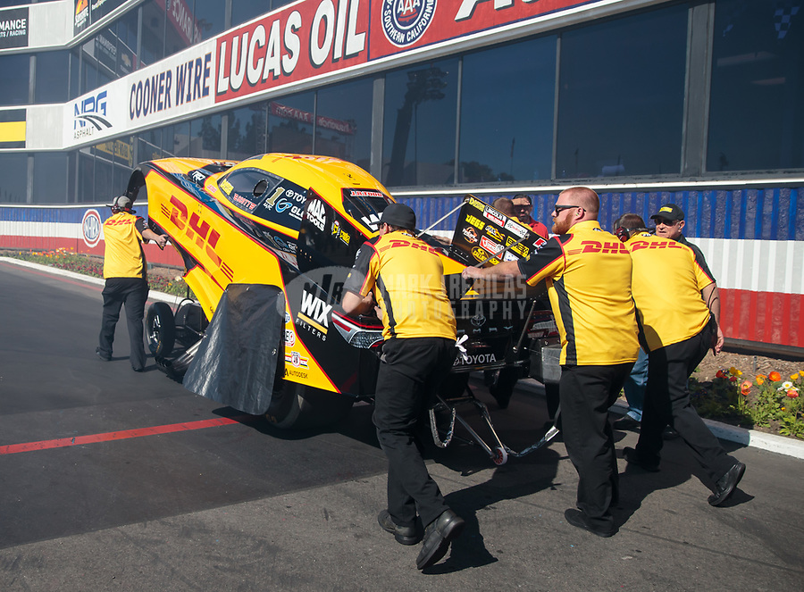 Feb 8, 2019; Pomona, CA, USA; Crew members push the car of NHRA funny car driver J.R. Todd during qualifying for the Winternationals at Auto Club Raceway at Pomona. Mandatory Credit: Mark J. Rebilas-USA TODAY Sports