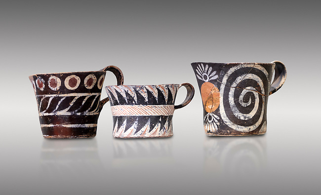 """Minoan Kamares """"eggshell"""" ware cups with  with  polychrome decorations, from set found at Phaistos Palace 1800-1600 BC; Heraklion Archaeological  Museum, grey background.<br /> <br /> These cups found as parts of sets in Phaistos palace were names """"eggshell"""" ware due to the very thin walls of the cups. This style of pottery is named afetr Kamares cave where this style of pottery was first found"""