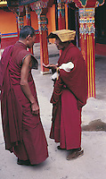 Two monks, both dressed in their traditional robes and one wearing a strange hat peculiar to his order, converse in the Jokhang Temple, Lhasa, Tibet.