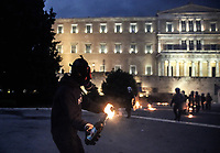 Pictured: A protester throws a petrol bomb to riot police officers on the steps of the Parliament Thursday 18 May 2017<br /> Re: Clashes between anti fourth memorandum protesters and riot police in front of the Parliament building in Syntagma Square, Athens, Greece