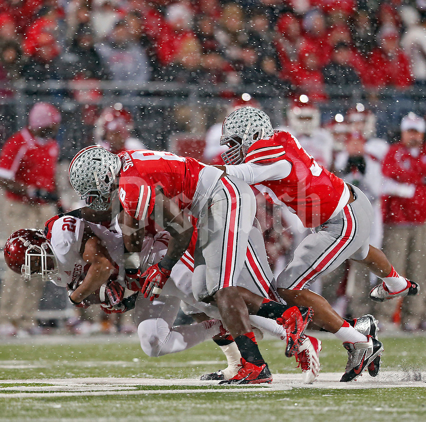 Ohio State Buckeyes defensive lineman Noah Spence (8), Ohio State Buckeyes defensive lineman Adolphus Washington (92) and Ohio State Buckeyes linebacker Joshua Perry (37) take down Indiana Hoosiers running back D'Angelo Roberts (20) in the backfield during the third quarter of their college football game at Ohio Stadium in Columbus, Ohio on November 23, 2013.  (Dispatch photo by Kyle Robertson)