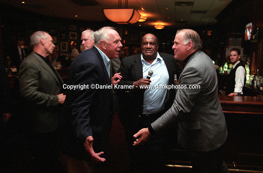 Bob Skoronski and Jerry Kramer goof around during the auction portion of the evening as Willie Davis conducts the sales during the Lombardi's Legends reunion at Lombardi's Steakhouse in Appleton, Wisconsin.