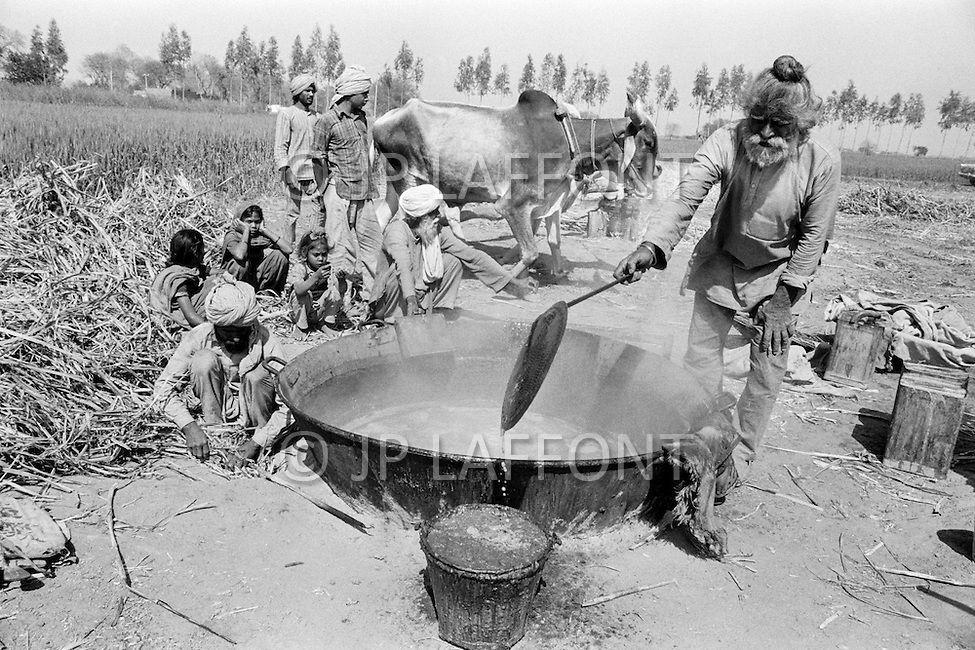 1970, Punjab, India --- A farmer heats sugar cane in the Punjab. --- Image by © JP Laffont