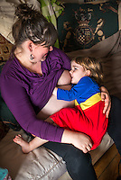 "A woman  8 months pregnant breastfeeds her little girl aged 3 years old on a sofa in the living room. They are looking at each other.<br /> <br /> <br /> Image from the ""We Do It In Public"" documentary photography project collection: <br />  www.breastfeedinginpublic.co.uk<br /> <br /> Dorset, England, UK<br /> 14/02/2013"