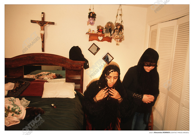 Zulayka Martinex, 28, (left) a Muslim, prays with a friend at the home of her Catholic sister, she was visiting after her nieces and nephewes were baptized; Houston, Texas, May 2002