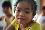 A girl smiles for a photograph at a center for children who have been affected by dioxin exposure in the village of Hoa Nhon, near Da Nang, Vietnam. The Da Nang Association of Victims of Agent Orange/Dioxin says that more than 1,400 children around the city suffer from mental and physical disabilities because of dioxin exposure, a legacy of the U.S. military's use of Agent Orange and other herbicides during the Vietnam War more than 40 years ago.  About 60 children attend the Hoa Nhon center each day. Many of them have mental disabilities or they cannot hear or speak. Children are taught to read and write, sew clothes, make handicrafts and help their families raise crops and livestock. Children who cannot hear or speak are taught sign language. The Vietnam Red Cross estimates that 3 million Vietnamese suffer from illnesses related to dioxin exposure, including at least 150,000 people born with severe birth defects since the end of the war. The U.S. government is paying to clean up dioxin-contaminated soil at the Da Nang airport, which served as a major U.S. base during the conflict. But the U.S. government still denies that dioxin is to blame for widespread health problems in Vietnam and has never provided any money specifically to help the country's Agent Orange victims. May 29, 2012.