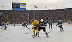 Michigan forward A.J. Treais (21) fights for posession of the puck with Michigan State forward Trevor Nill (A), in the first period of the Big Chill at the Big House NCAA college hockey game at Michigan Stadium in Ann Arbor, Mich., on Saturday, Dec. 11, 2010. (AP Photo/Tony Ding)