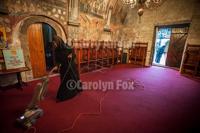 A nun vacuums the carpet of the narthex within the church at the Monastery Mileševa, Serbia originally built in the 13th century.
