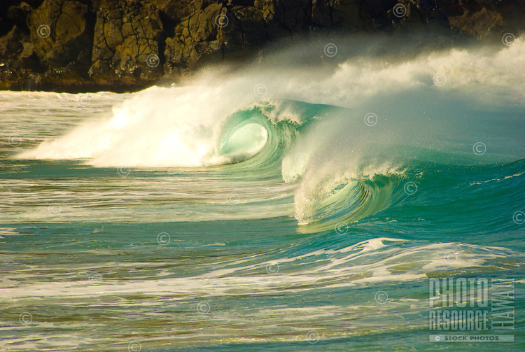 A Beautiful large wave creates two barrels in the powerful shorebreak at Waimea Bay, on the North Shore of Oahu.