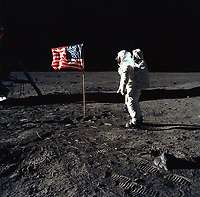 "(20 JULY 1969) --- Astronaut Edwin E. Aldrin, Jr., lunar module pilot of the first lunar landing mission, poses for a photograph beside the deployed United States flag during an Apollo 11 Extravehicular Activity (EVA) on the lunar surface. The Lunar Module (LM) is on the left, and the footprints of the astronauts are clearly visible in the soil of the Moon. Astronaut Neil A. Armstrong, commander, took this picture with a 70mm Hasselblad lunar surface camera. While astronauts Armstrong and Aldrin descended in the LM, the ""Eagle"", to explore the Sea of Tranquility region of the Moon, astronaut Michael Collins, command module pilot, remained with the Command and Service Modules (CSM) ""Columbia"" in lunar-orbit."