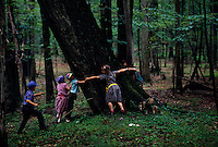 Children hold hands and circle a large tree to measure it while hiking in the woods. School children from the Bruderhof community take walks in the historic woods near their home.