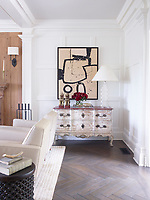 In the living room, the panelled walls are decorated in off-white and neutral tones, the mid-century furnishings include Harvey Probber armchairs. Modern art hangs above an antique sideboard given a distressed finish.