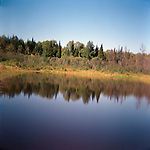 Landscape view of lake and surrounding wooded area in Autumn