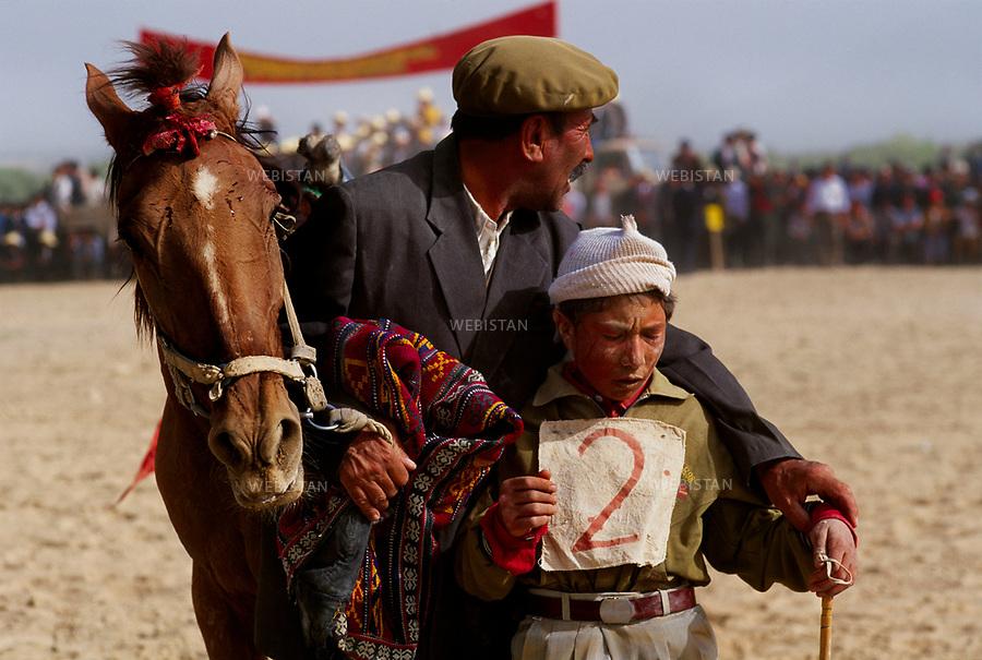1995. A young Kyrgyz rider is cheered up by his father after he fell from his horse during a race in the plain of Mazar for the 40th anniversary of the &quot;independence&quot; of Taxkorgan Tajik Autonomous County. Un jeune cavalier kirghize se fait consoler par son p&egrave;re, apr&egrave;s sa chute de cheval, pendant une course dans la plaine de Mazar lors du 40e anniversaire de &quot;l'ind&eacute;pendance&quot; du comt&eacute; autonome tadjik de Taxkorgan.<br /> HEMIS diffusion