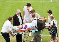 17-6-09, Rosmalen, Tennis, Ordina Open 2009, Raemon Sluiter kijkt bezorgd toe hoe Marcus Baghdatis  met de brancar wordt afgevoerd nadat hij in zijn partij tegen Sluiter zijn knie heeft verdraaid