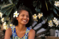 A pretty Filipino Hawaiian woman with a plumeria flower in her hair smiles.