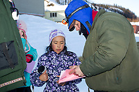 Young Angelina Hamilton gets an autograph from Bruce Linton at the Shageluk village checkpoint during the 2011 Iditarod race.