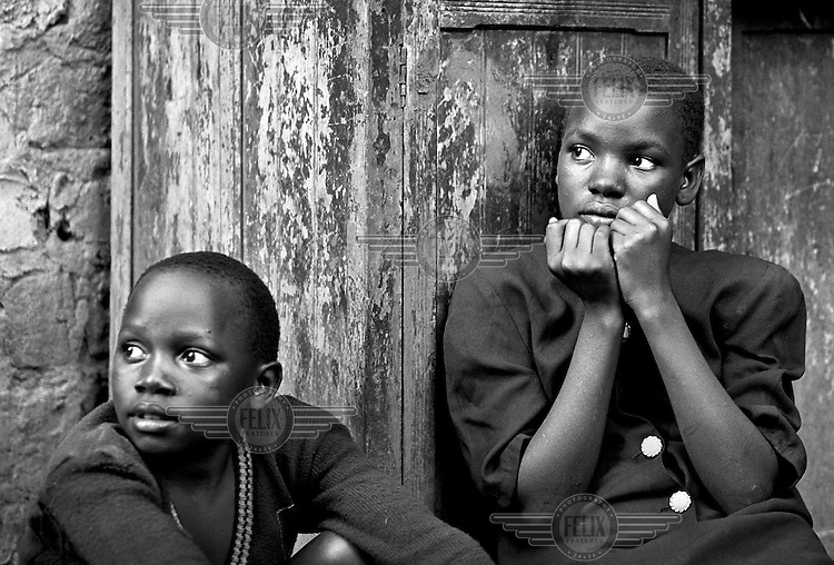 Two teenage girls sit outside their house in Kampala, Uganda on April 28, 2001. Their mother is very ill with AIDS. More than 13 million African children have been orphaned by the the AIDS pandemic. Worldwide, more than 20 million people have died since the first cases of AIDS were identified in 1981.