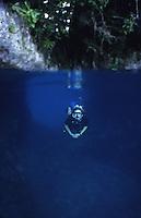 Diver swimming through cave