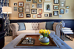The living room in Kent and Jenny Longardner's home in Elmhurst, Illinois, after Design Star winner and Host Meg Caswell 's redesign, as seen on HGTV's Great Rooms, season 2 .<br /> The built-in library opens to unveil the door to the office, the tikky bar is in a corner and the facing wall is covered with a display of framed photos.