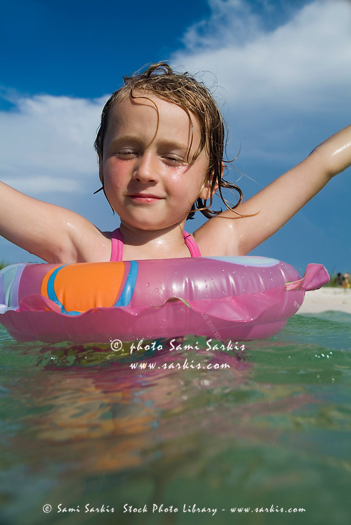 Little blond girl swimming in the tropical water at Cayo Jutias, Cuba.
