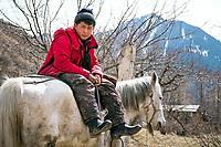 A boy sits on his horse outside Karakol, Kyrgyzstan