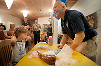NWA Democrat-Gazette/DAVID GOTTSCHALK Finn Ramser, 4, prepares to pick up his glazed donut Wednesday, October 3, 2018, after adding sprinkles with the help of Corporal Dallas Brashears during the Fayetteville Police Department Coffee with a Cop event at Rick's Bakery in Fayetteville. Members of the department, including Chief of Police Greg Tabor, were on hand to visit with members of the community to answer questions, listen to concerns and get to know the officers. Free coffee and a donuts sprinkle bar were available.