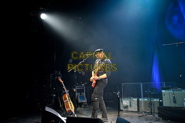 Richard Thompson.performing in concert, Shepherd's Bush Empire, London, England. .25th February 2013.on stage lie gig performance music side profile full length hat flat cap scarf black shirt trousers guitar goatee facial hair .CAP/MAR.© Martin Harris/Capital Pictures.