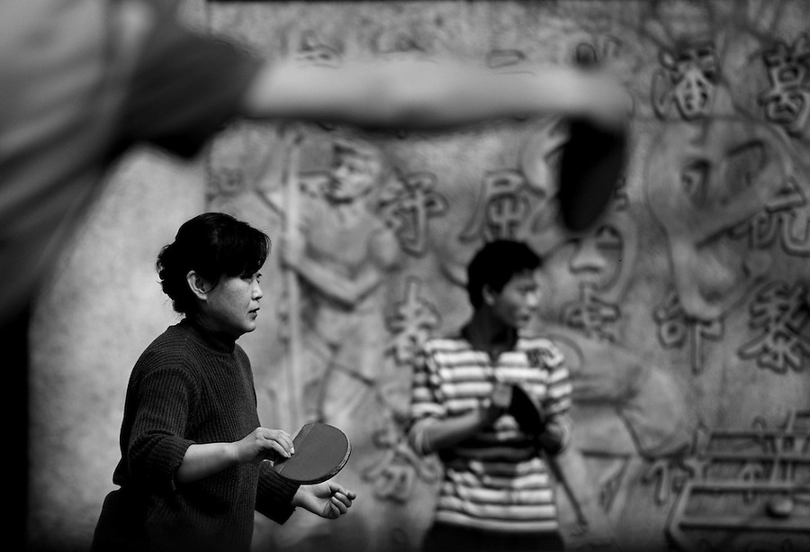 Beijing residents play table tennis in a public park.