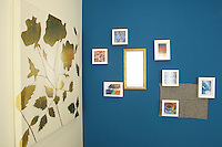 Canvas, picture frames, and a mirror on colored walls as wall decorations.