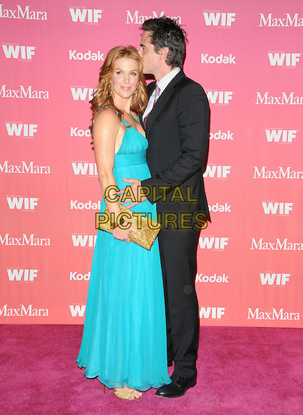 POPPY MONTGOMERY & ADAM KAUFMAN .at The Women in Film 2009 Crystal .and Lucy Awards held at The Hyatt Regency Century Plaza in Century City, California, USA, June 12th 2009                                                                     .full length black suit couple turquoise dress gold clutch bag bracelets hugging arm around kissing long maxi .CAP/DVS.©Debbie VanStory/RockinExposures/Capital Pictures