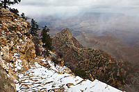 Snow highlights the upper section of the Grandview trail, below the South Rim of the Grand Canyon.  The trail goes to Horseshoe Mesa, seen below through the clouds.  A lower section of the trail can be seen in the lower right corner.