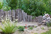 Sandarium im Garten, am Rand mit Totholzhaufen und Steinhaufen als zusätzliche Nisthilfen, Unterschlupfmöglichkeit für Tiere. Sandarium, Sand, Sandfläche, Sandhaufen im Garten, Naturgarten, Nisthilfe für Wildbienen und solitäre Wespen, Lebensraum für Eidechsen, Eidechse. Soll verschiedenen Insekten als Unterschlupf, Nistplatz, und Nahrungsquelle dienen. Mehr als die Hälfte der Wildbienenarten, welche Nester bauen, nisten im Erdboden. Wildbienen-Nisthilfen, Wildbienen-Nisthilfe selbermachen, selber machen, Wildbienenhotel, Insektenhotel, Wildbienen-Hotel, Insekten-Hotel, Eichenspaltpfähle mit Bohrlöchern, Eichenspaltpfahl, Holz, Löcher mit verschiedenen Durchmesser, Wildbienen-Nisthilfe aus Holz, Längsholz, Hartholz