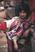 A young girl with her baby sister in a shawl on her back, Maras, near the Sacred Valley of the Incas in Peru.