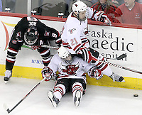 UNO's Terry Broadhurst shoulders the weight of teammate Matt White after getting tangled up with St. Cloud State's Garrett Roe. Nebraska-Omaha rallied from a 3-0 deficit to beat St. Cloud State 4-3 Saturday night at Qwest Center Omaha.  (Photo by Michelle Bishop)