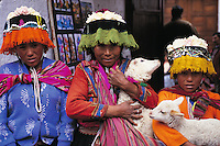 Three children, who are dressed in traditional clothing, holding lambs in Ambato Market, Ecuador.