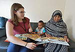 Christine Baer, a congregational resource developer with Church World Service in Lancaster, Pennsylvania, helps Mekiya Kebir and her 2-year old son Hashim read a book as she delivers a backpack full of books and art supplies to the recently arrived Eritrean refugee family. Church World Service resettles refugees in Pennsylvania and other locations in the United States. <br /> <br /> Photo by Paul Jeffrey for Church World Service.
