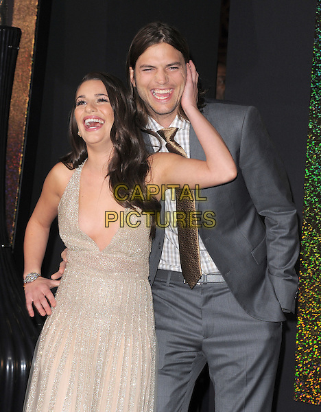 "Lea Michele & Ashton Kutcher.The World Premiere of ""New Year's Eve' held at The Grauman's Chinese Theatre in Hollywood, California, USA..December 5th, 2011.half length grey gray suit jacket stubble facial hair check shirt white yellow tie gold beige dress low cut plunging neckline cleavage smiling laughing funny hand on hip cheek face .CAP/RKE/DVS.©DVS/RockinExposures/Capital Pictures."